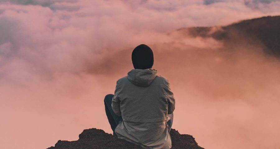 A man sitting at the top of a mountain looking at beautiful cloudy sky.