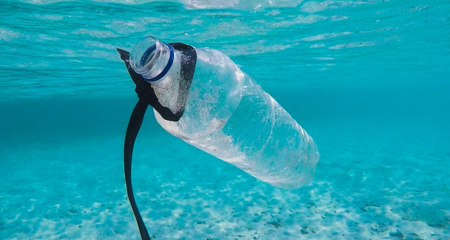 Plastic waterbottle floating underwater in ocean.