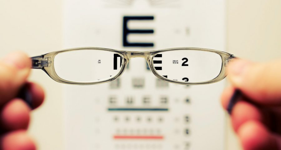 Person holding glasses to eye chart