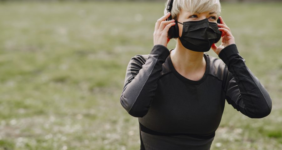 A woman using a mask and listening music using headphones