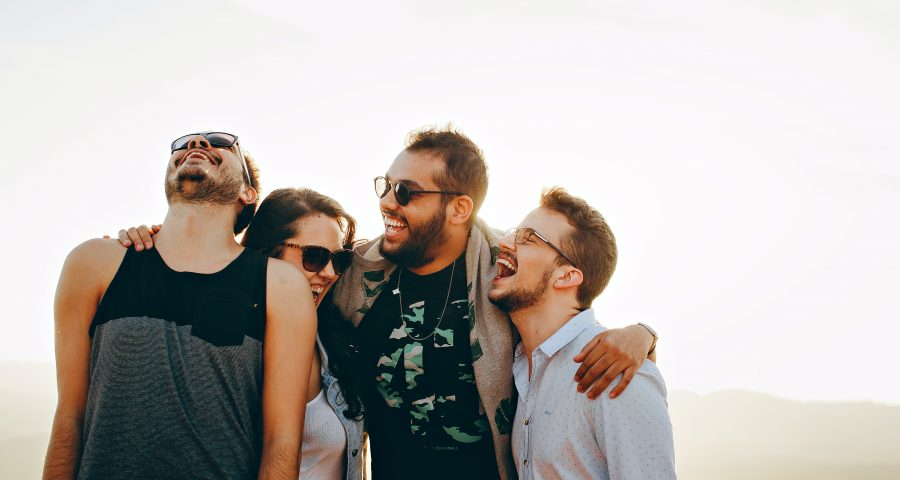 A group of four friends hug and laugh on a sunny day