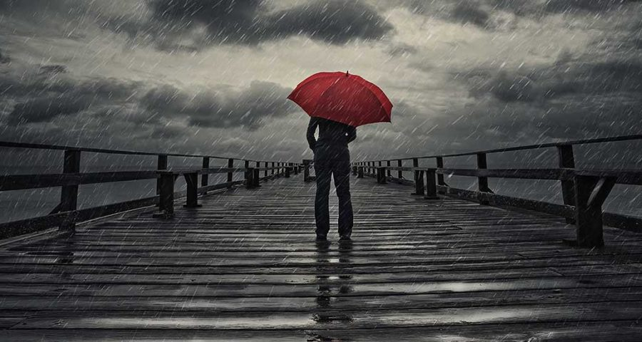 Bridge with a person with a red umbrella in the middle while it is raining