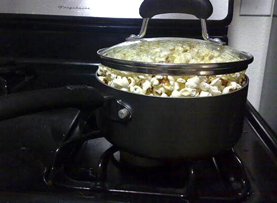 A pot with overfloading popcorn on a gas stove