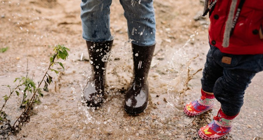 Feet of two people wearing raining boots jumping in the mud