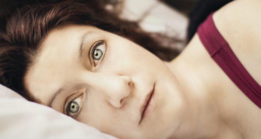 Woman resting in bed with her eyes opened, looking at the camera