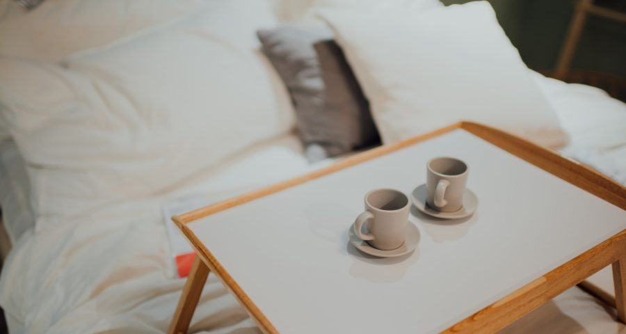 Two cups of coffee on a potable table placed on a bed