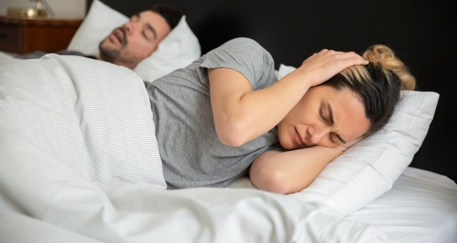 Man sleeping and snoring with woman nexo to him with her hands on her ears