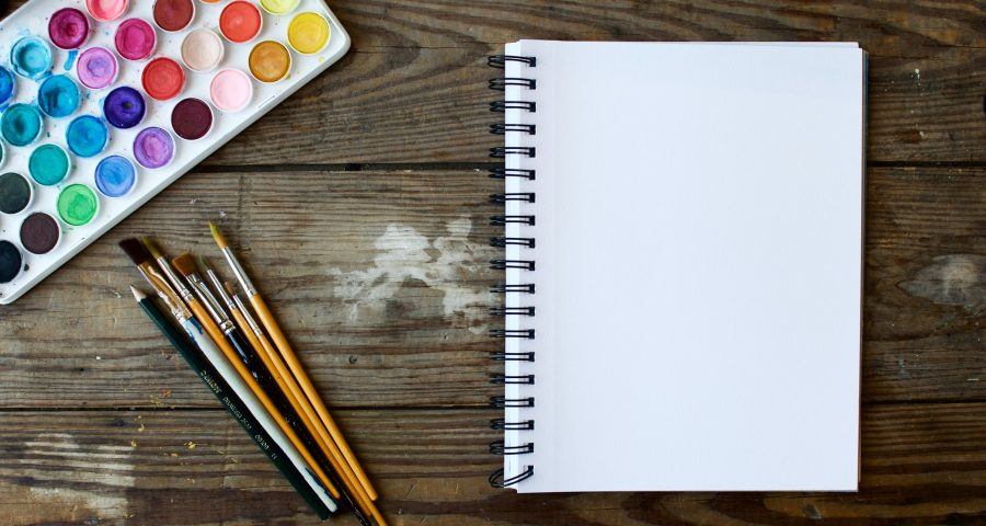Watercolor colors, brushes, and a notebook on a wooden table