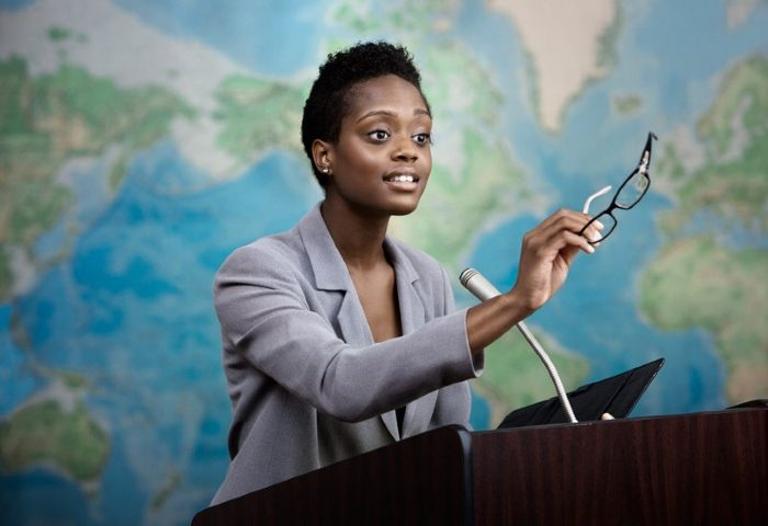A Black woman giving presentation with left-hand lifted to emphasis a point.