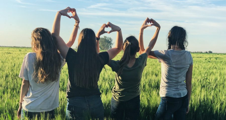 Women forming heart gestures during daytime in a grass field