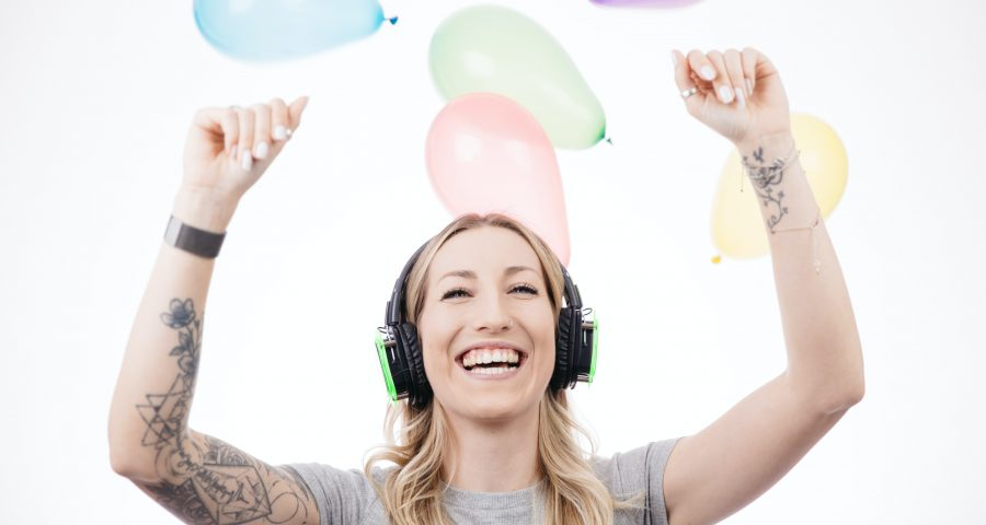 Picture of female with tattoo smiling with headphones.