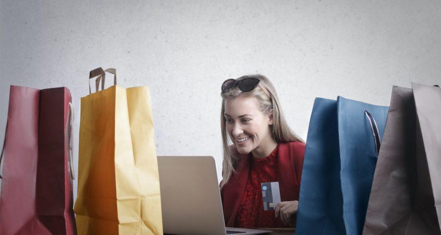 Colorful shopping bags surrounding a woman doing online shopping.