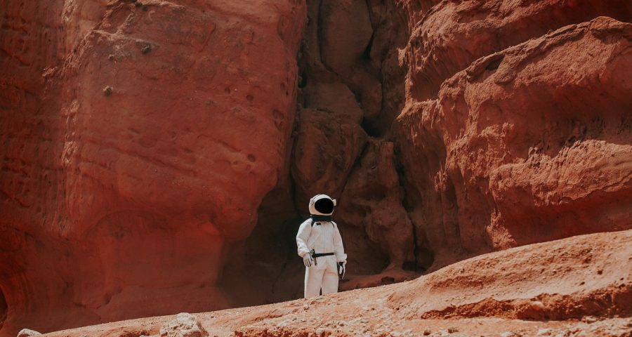 Image of astronaut with red mountains behind him.