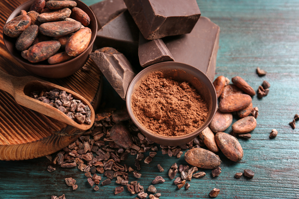 Bowls of cocoa beans and powder with broken chocolate pieces on color background from depositphotos.com