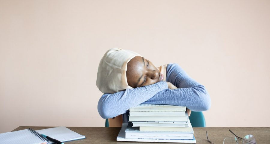 Image of young girl napping on textbooks.