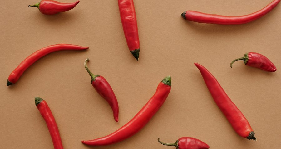 Red hot peppers on orange background.