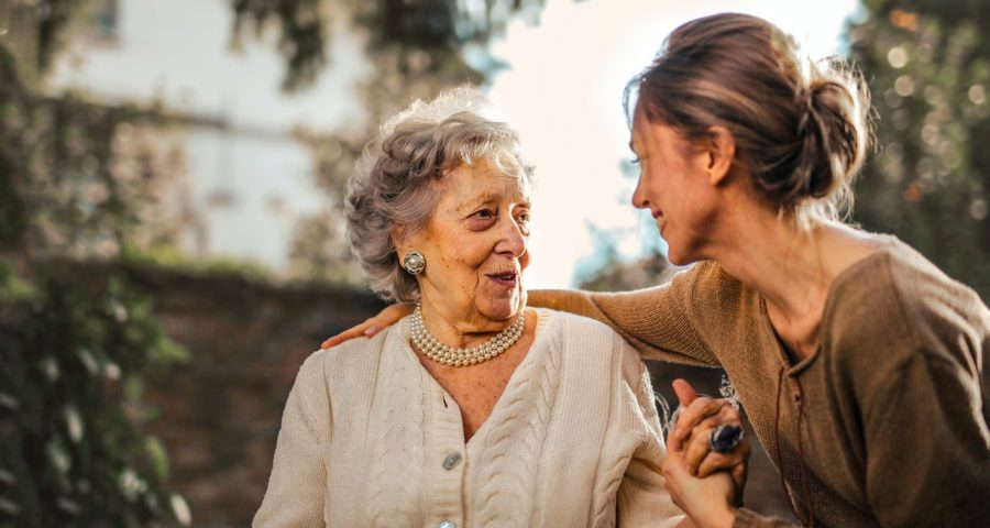 Image of old lady and young woman holding hands.