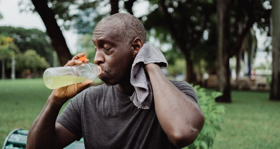 Man sweating and drinking yellow-colored fluid.